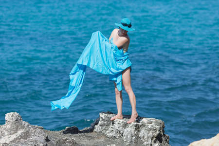 Middle aged woman in blue hat and sarong posing on rocky seashore. Woman in pareo against the sea