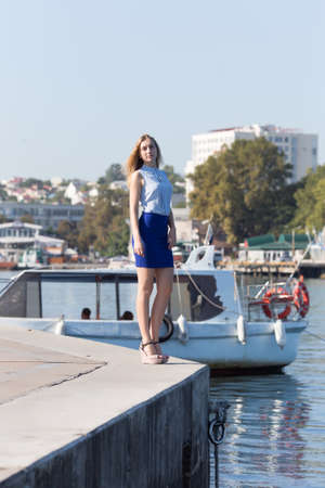 Blonde girl in seaside town. Tall young woman in short skirt and sleeveless blouse posing against bay Stok Fotoğraf