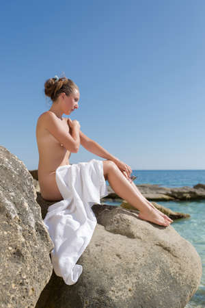 Girl sunbathing on rocky seashore. Naked young woman with white beach towel on her knees sits on rock and looks at the sea