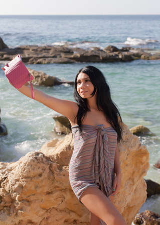 Dark haired young woman resting in a secluded place of wild rocky seashore. Long haired brunette in sarong makes selfie against sea
