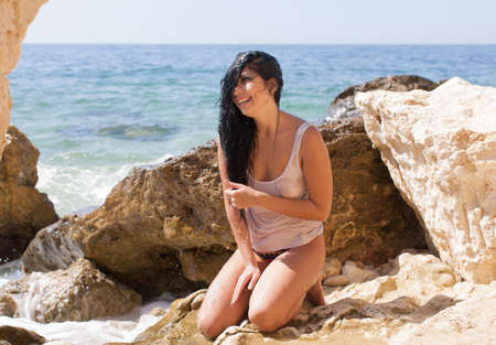 Young brunette woman in wet tank top kneeling on rocky beach. Wet girl laughing after taking unexpected shower from wave
