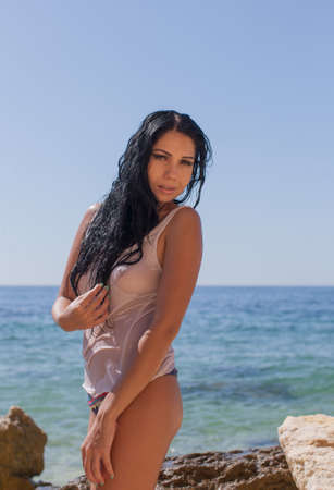Dark haired young woman posing in wet tank top at rocky beach. Portrait of attractive sexy brunette woman in wet transparent wear against sea