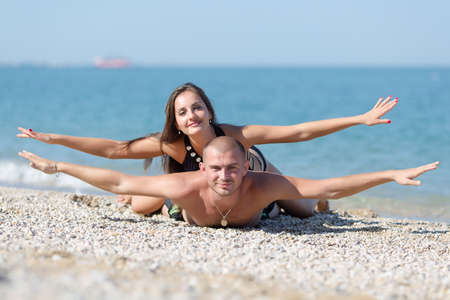Young woman lies on back of his guy. Attractive couple posing biplane with arms outstretched looking at camera smiling Stock Photo