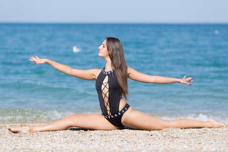 Long-haired girl in fashionable one-piece swimsuit on beach. Young woman doing gymnastic twine with arms outstretched