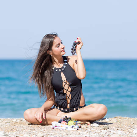 Long-haired girl in fashionable one-piece swimsuit on beach. Girl sits with legs crossed and eats black grapes against sea