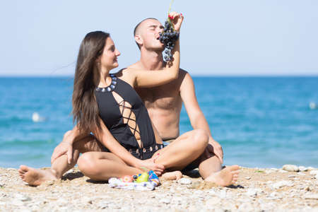 Attractive couple flirting on beach. Girl sits between legs of guy and feeds him with black grapes