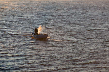 Seascape in time of sunrise. Motor boat floats in sea in morning time