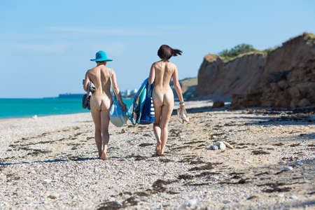 Two naked women with their belongings in hands going along deserted beach. Homosexual couple walking along pebble beach