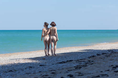 Seashore with naked same-sex couple. Two nude female persons going along seashore in morning time, rear view