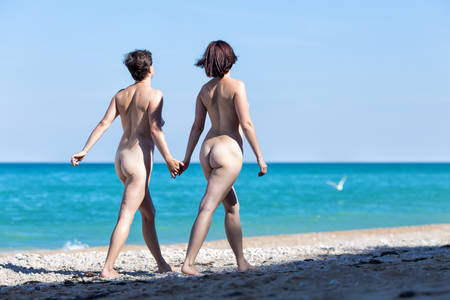 Homosexual couple at the sea. Two naked female persons walking holding hands along seashore in morning time, rear view