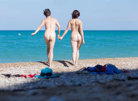 Homoseksueel paar op kiezelstrand. Twee naakte vrouwelijke personen hand in hand gaan op grind naar de zee, achteraanzicht