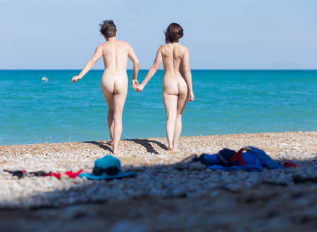Homosexual couple on pebble beach. Two naked female persons holding hands going on shingle to the sea, rear view Standard-Bild