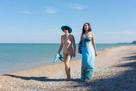 Homosexual couple at the sea. Two female persons 30 and 40 years old walking along pebble beach 版權商用圖片