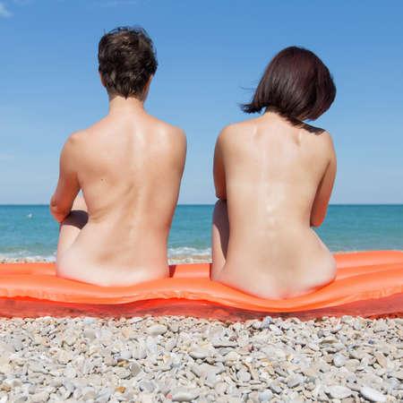 Homosexual couple on pebble beach. Two women 30 and 40 years sunbathing naked sitting on pool raft Stock Photo