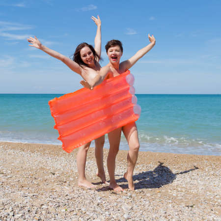 Homosexual couple on pebble beach. Two women 30 and 40 years standing with arms raised and screaming. Thay hiding their nudity behind inflatable pool raft