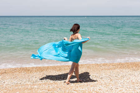 Girl in blue pareo on beach. Woman in blue sarong walks with arms outstretched along seashore