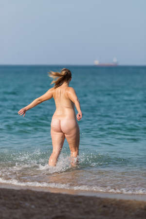 Overweight girl on the beach. Naked fat mid adult woman rushes into the sea Standard-Bild
