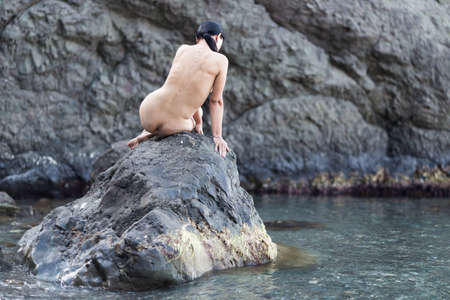 Brunette resting in a secluded place of wild rocky coast. Naked middle age woman sitting on rock and arching her back, rear view