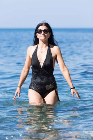 Three-quarters length portrait of middle age woman in sea. Brunette woman in one-piece swimsuit and sunglasses coming out from sea water Stock Photo