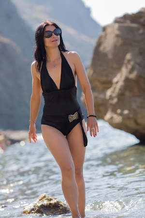 Portrait of middle age woman on beach. Brunette woman in one-piece swimsuit and sunglasses coming out from sea water Stock Photo
