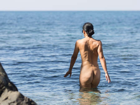 Skinny-Dipping. Naked dark haired middle aged woman entering in sea Banque d'images - 95715663