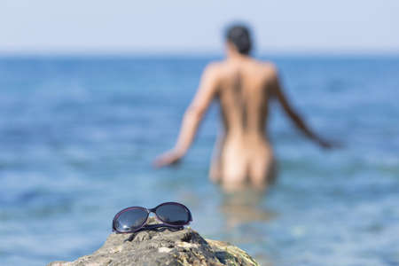 Skinny-Dipping. Naked dark haired middle aged woman entering in sea, focus on foreground