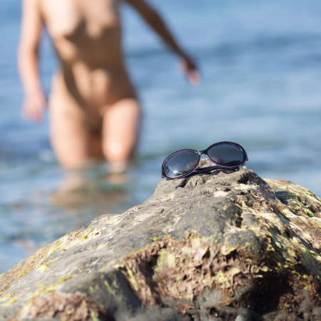 Skinny-Dipping. Naked woman comes from sea water, focus on foreground, square composition