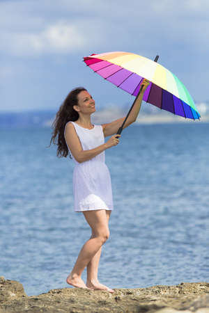 Curly girl at the sea. Young woman in white sleeveless dress opens rainbow umbrella Stock Photo
