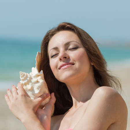 Portrait of slim girl with big shell of mollusk. Attractive young woman holds shell of mollusk and listens it with eyes closed and smile Stock Photo