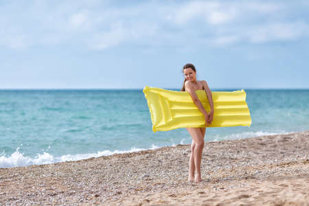 Young woman with yellow pool raft on pebble beach. Smiling female person hides her nudity behind  inflatable raft looking at camera Foto de archivo
