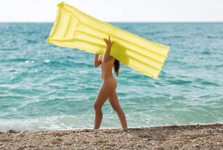 Girl with yellow pool raft walks along the sea. Naked young woman runs along seashore and hides her face behind  inflatable raft Archivio Fotografico