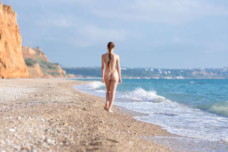 Slim girl with hair collected in a braid walks along seashore in evening time. Naked attractive young woman going on surf line, rear view