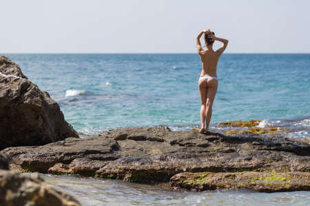 Attractive young woman on wild rocky seashore. Slim girl in white panties stands on rock against sea and adjusts her hairstyle, rear view Фото со стока