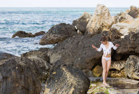 Attractive young woman on wild rocky seashore. Barefoot slim girl in white lingerie and knotted shirt with short sleeves walks among stones Stock Photo