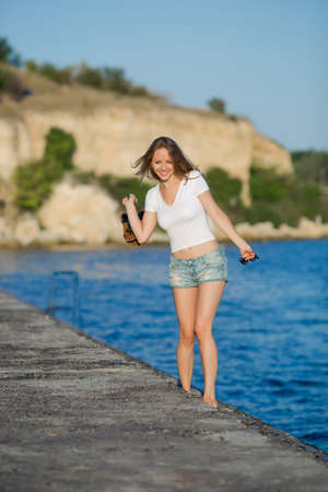 Barefoot girl in shorts walking on wet concrete quay. Young woman in white T-shirt with sandals and sunglasses in hands going along edge of pier in morning time