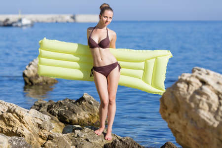 Attractive girl with yellow pool raft against sea. Beautiful young woman in brown bikini holds yellow inflatable raft on rocky seashore Stock Photo