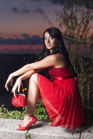 Portrait of young woman in red sleeveless dress. Attractive long haired brunette in red sundress posing in night park against sunset sky Stock Photo