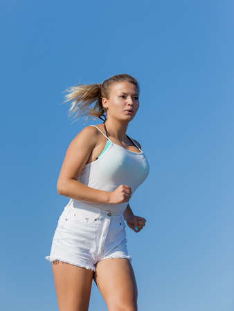 Jogging. Girl in white tank top and white jeans shorts running against clear sky 写真素材