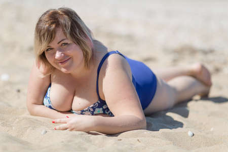 Overweight woman in blue one-piece swimsuit at the sea. Fat girl in blue swimwear lying on sand and looking at camera smiling Standard-Bild