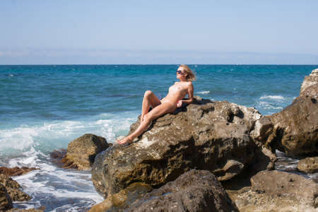 Girl resting on wild rocky beach in windy day. Naked woman in tinted sunglasses reclining sunbathes on rock by sea Standard-Bild
