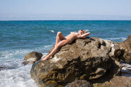 Girl resting on wild rocky beach in windy day. Naked woman in tinted sunglasses lying with arms behind head and knee bent on rock by sea