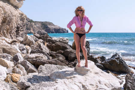 Girl resting on rocky beach in windy day. Barefoot woman in knotted pink shirt and black bikini bottom standing arms akimbo on stone against sea. She smiling and looking on camera through sunglasses Stock Photo