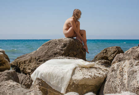 Naked bride. Woman sits on a stone on beach behind dress laid out on stones