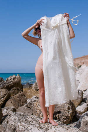 Naked bride. Woman standing on stone on beach, holding bridal dress and hiding behind it
