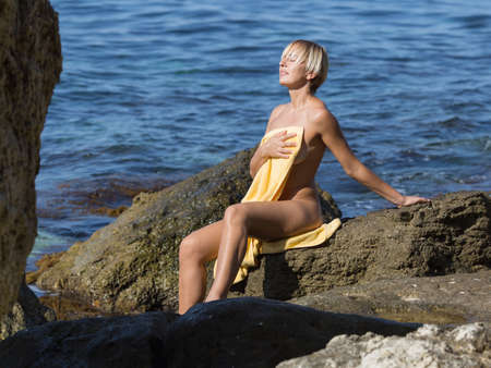 Short-haired blond woman resting in a secluded area of wild rocky seashore. Naked girl sitting on stone and drying her body with a towel on wild rocky beach Banque d'images