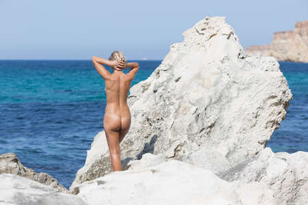 Middle aged woman resting in a secluded area of wild rocky seashore. Tanned blond woman stands among white rocks with hands behind head, rear view 스톡 콘텐츠