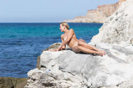 Middle aged woman resting in a secluded area of wild rocky seashore. Naked blond woman sunbathes reclining among white rocks