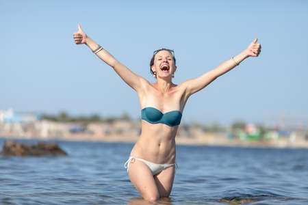 Portrait of happy girl in sea.  Middle aged woman in swimsuit standing knee-deep in sea water, shows thumbs up by both hands and shouts 版權商用圖片