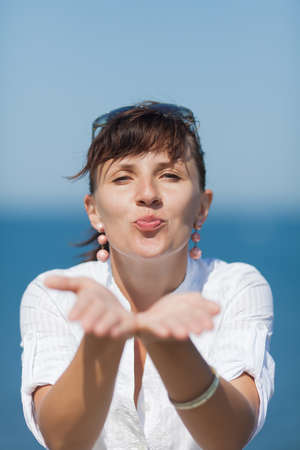 Portrait of middle aged woman against sea. Girl in white blouse sends an air kiss by both hands Stock Photo