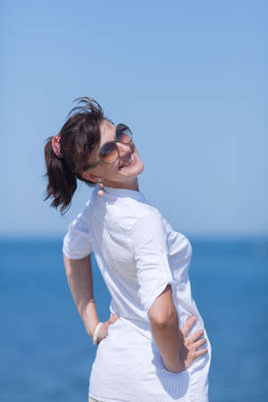 Portrait of middle aged woman against sea. Girl in white stands with arms akimbo and looks over shoulder smiling Фото со стока